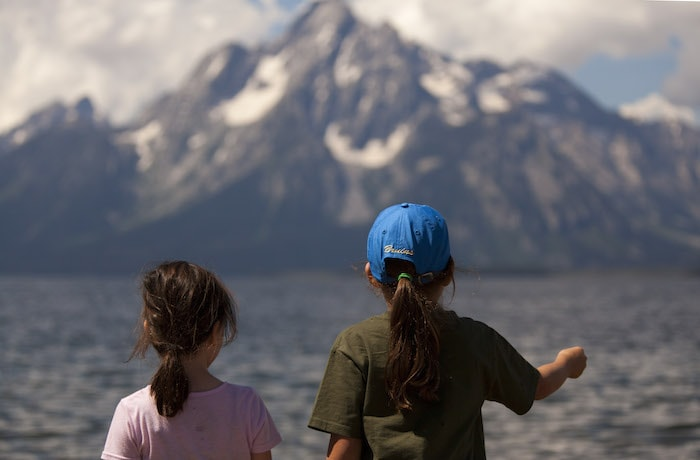 Young explorers look out over Jenny Lake to the snow-covered peaks of the Grand Tetons.