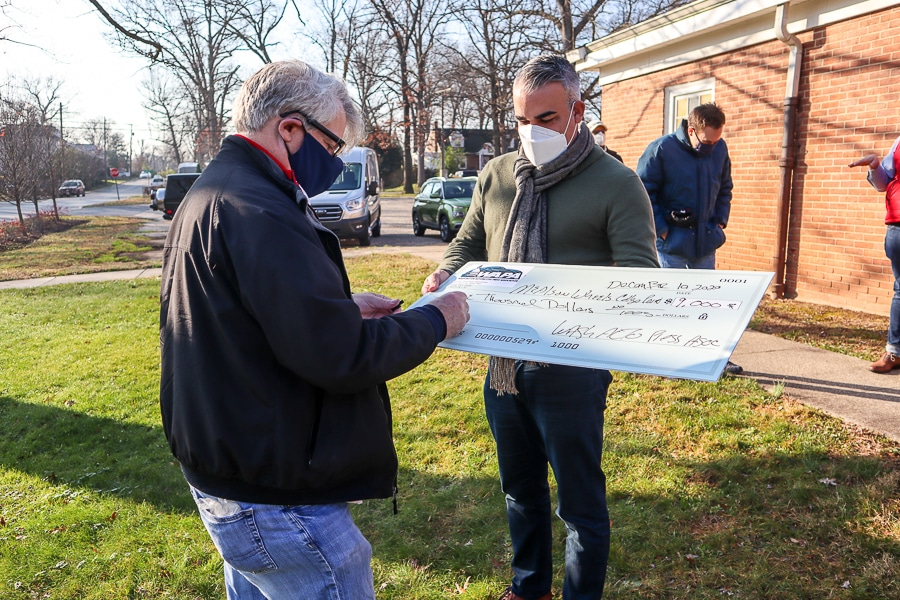 Signing a check from WAPA to Meals on Wheels